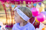 little girl wearing a top knot headband with her name