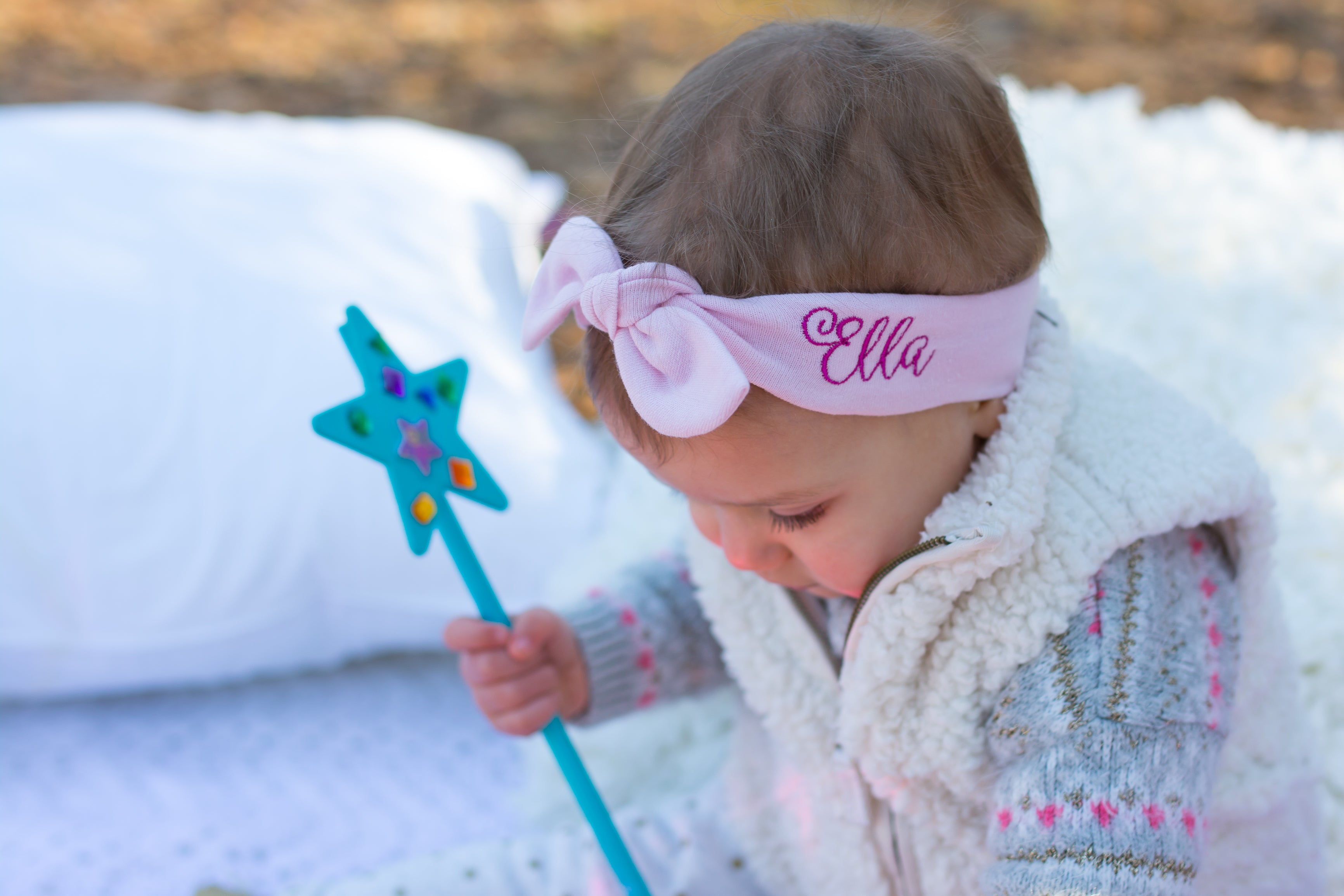 little girl with a star wand wearing a top knot headband with her name one it