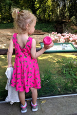 little girl looking at flamingos wearing a pink pineapple dress