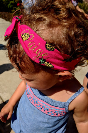 "baby modeling pink pineapple top knot headband with ""Paige"" embroidered in gold thread"