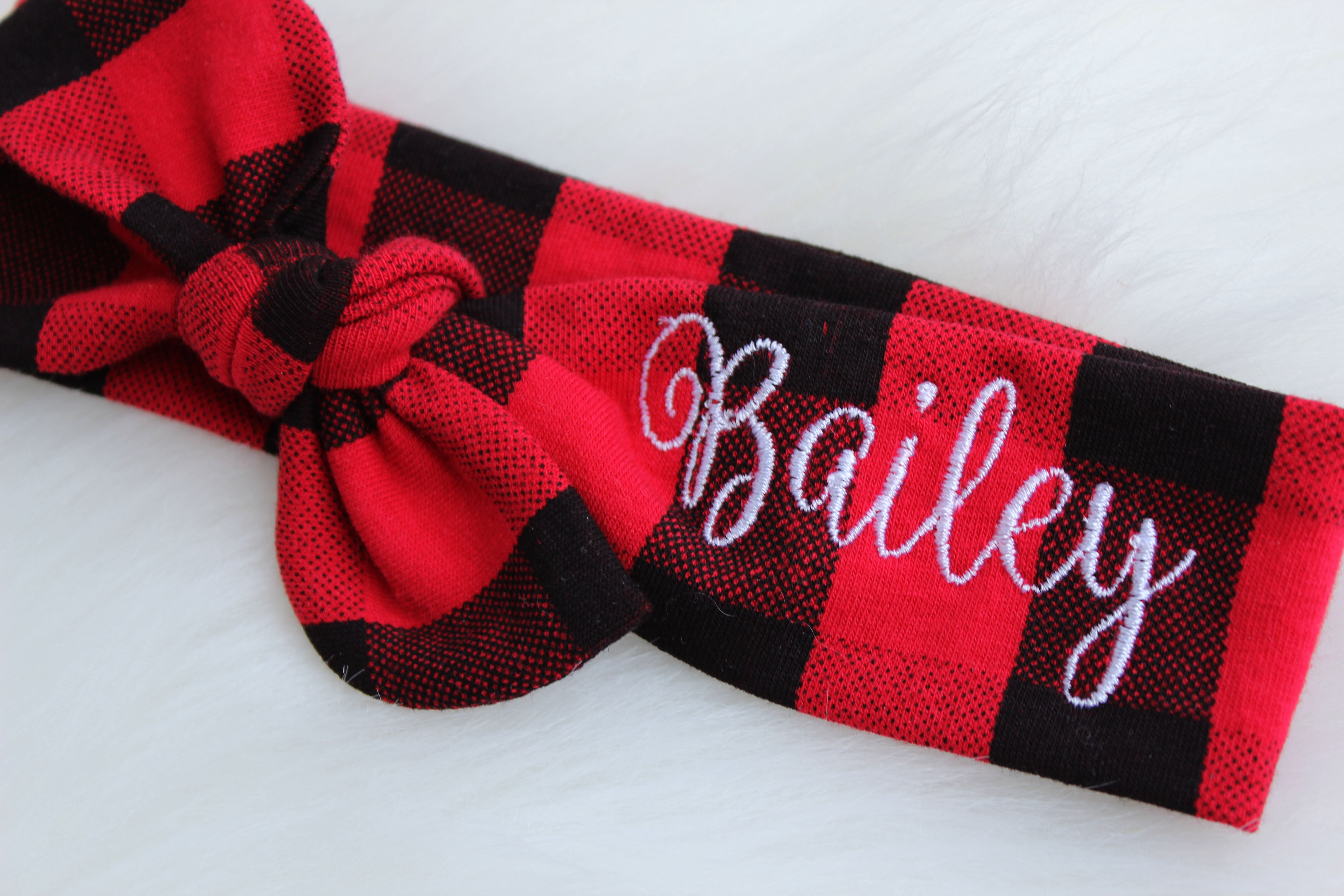 personalized baby headband with red and black buffalo plaid print with Bailey embroidered in white