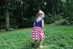 girl wearing tank top dress for 4th of july with blue stars and red and white stripes