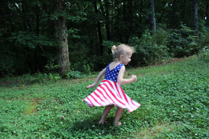 girl twirling in fourth of july dress
