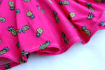 close up of skirt of pink pineapple print little girls dress