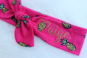 "pink pineapple top knot headband with ""Paige"" embroidered in gold"