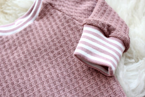 closeup of pink and white striped wristbands on mauve pink shirt
