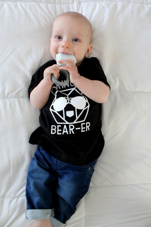 baby boy chewing on ring teether wearing black ring bear tshirt