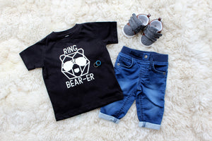 flat lay of ring bearer tshirt with baby jeans and shoes