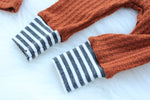 closeup of charcoal grey and white ankle bands on bottom of rust waffle knit baby pants