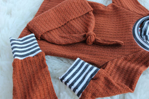 closeup of rust orange waffle knit baby boy outfit with shirt pants and hat