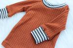 orange waffle knit baby shirt with grey striped wristbands