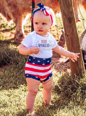 baby girl wearing star spangled sweetheart bodysuit and american flag bummies and headband