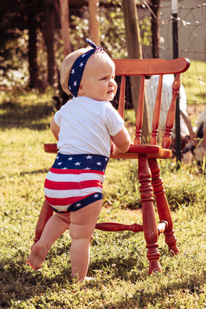 little girl in highwaisted bummies and top knot headband with with american flag fabric