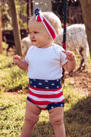 baby girl in stars and stripes highwaisted bummies shorts with top knot headband