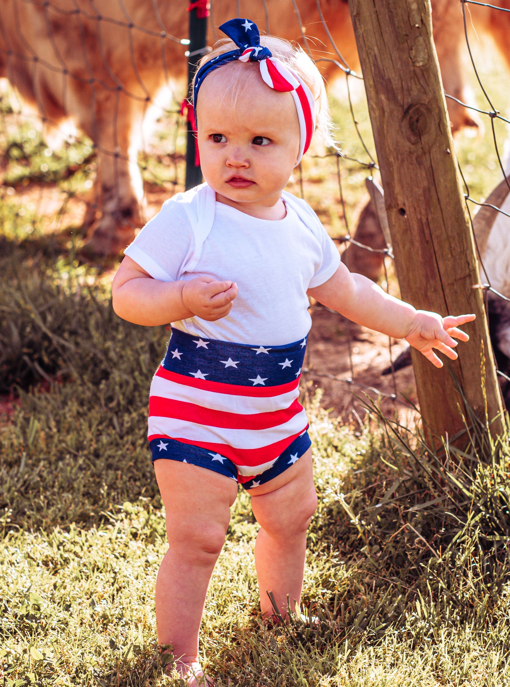 toddler girl wearing a diaper cover  with stars and stripes and patriotic headband