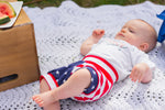 baby boy laying down on picnic blanket in american flag shorts