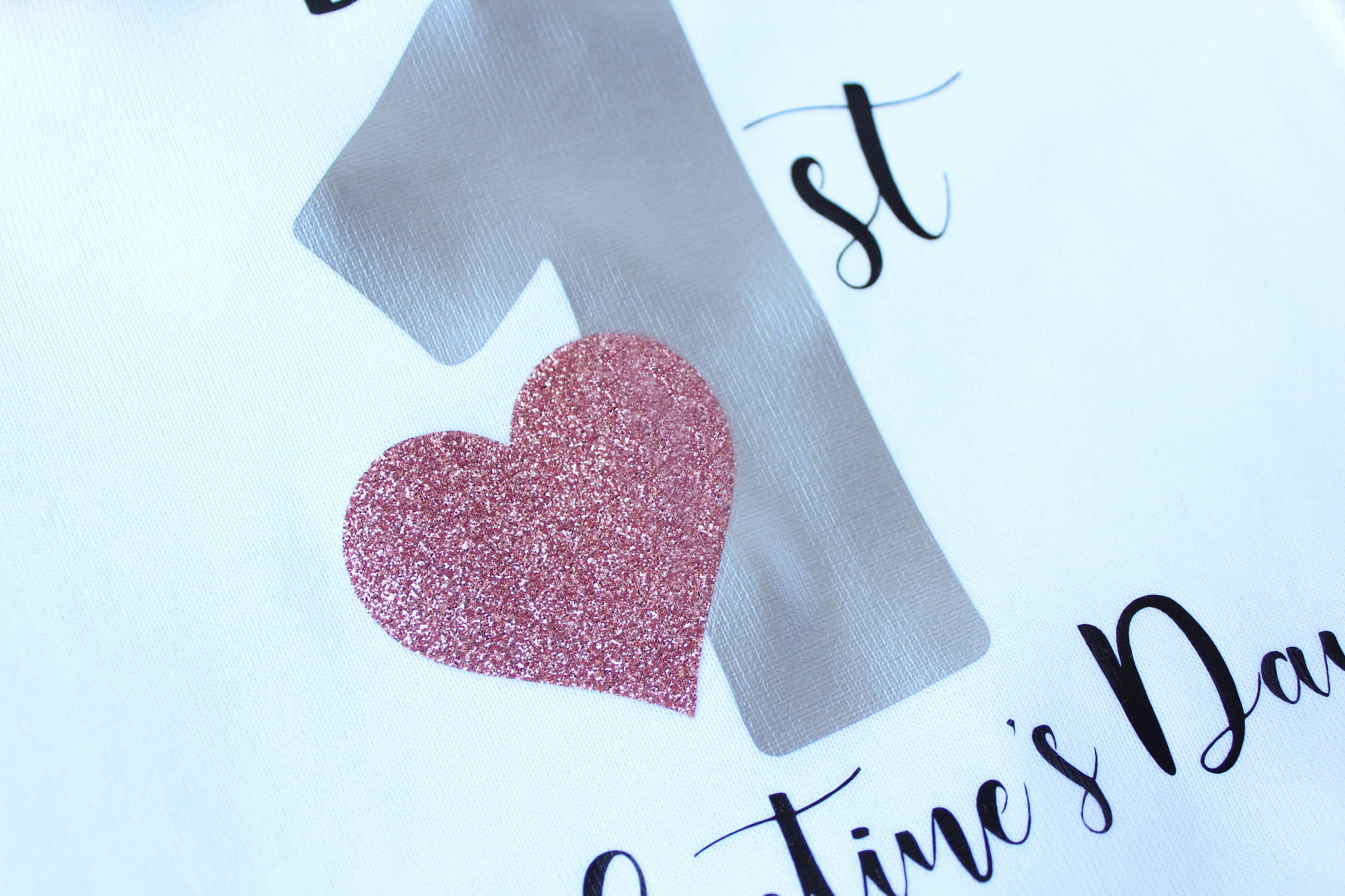 Closeup up vinyl 1st valentine's day shirt and gold glitter heart