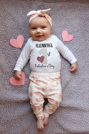 Baby wearing a shirt that reads Brinley's 1st valentine's day with leggings an top knot hat