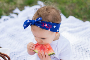 "girl eating watermelon wearing blue and white star top knot headband with ""Paige"" embroidered in red"