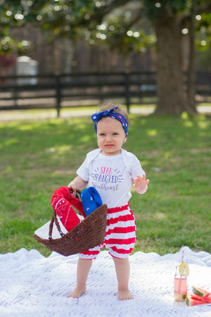 baby girl holding a basket wearing a 4th of july outfit