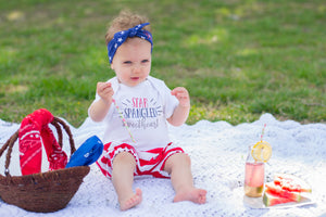 "Toddler girl eating watermelon wearing ""star spangled sweetheart"" bodysuit with red and white striped bubble shorts and blue and white star top knot heaband"