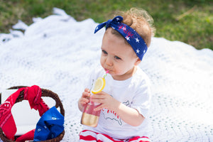 "girl drinking lemonade at picnic wearing personalized headband with ""Paige"" embroidered in red"