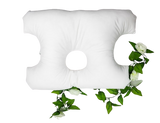 A standard size pillow with the corners cut off at an angle, with a 4 inch hole in the center and side cut outs that look like half moons on both sides.