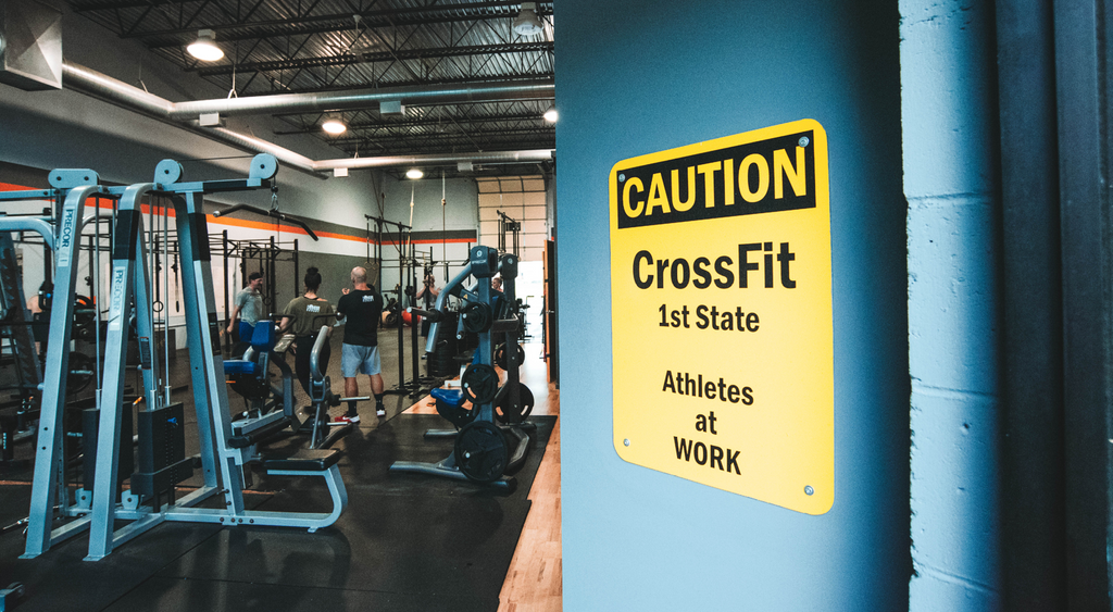 Forever Hungry gym interior with caution crossfit first state athletes at work sign on blue wall.