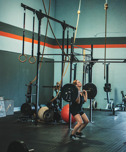 Female athlete working out and lifting heavy barbell inside Forever Hungry Athletics gym.