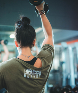 Athlete lifting barbell weight over head wearing Forever Hungry Athletics fitness apparel.