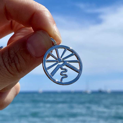 Hand holding a Sterling Silver Haleakala Pendant in front of the ocean
