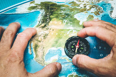 Hand holding compass on map of north america