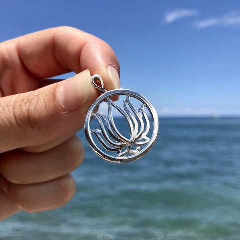 Hand holding sterling silver lotus pendant in front of the ocean