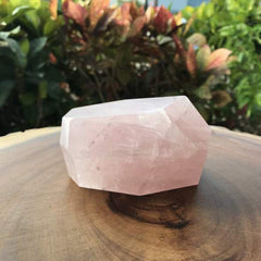 Polished Rose Quartz Crystal sitting on wooden table