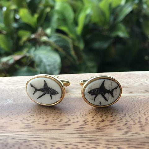 Scrimshaw Shark cuff links on a wood surface in front of plants
