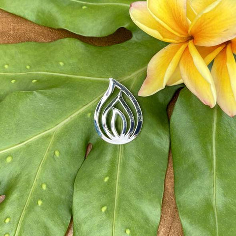 Sterling Silver Pele's Tear Pendant on a tropical leaf next to a yellow flower