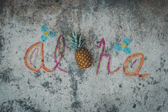 Aloha written in sand with pineapple