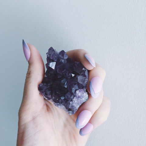 Woman's hand holding a large amethyst stone in front of a white wall