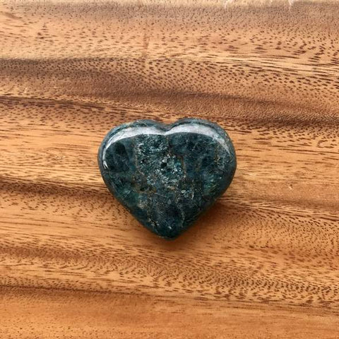 apatite heart stone on a wooden surface
