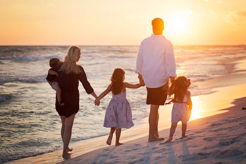 Family walking while holding hands on the beach during sunset