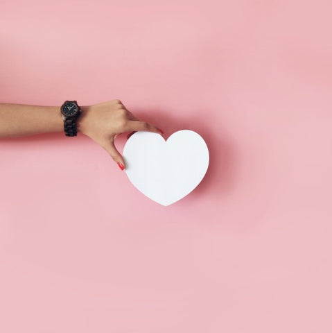 Hand holding a white heart on top of a pink background