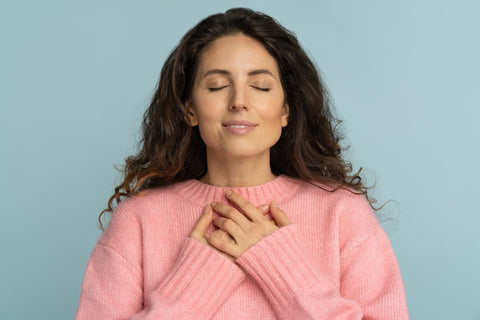 Woman with eyes closed and both hands on her heart