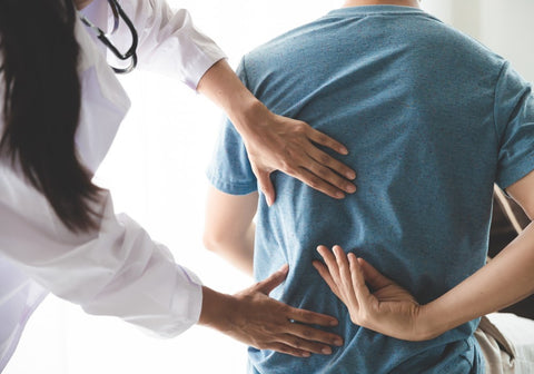 Woman doctor looking for pain by pressing on patients back