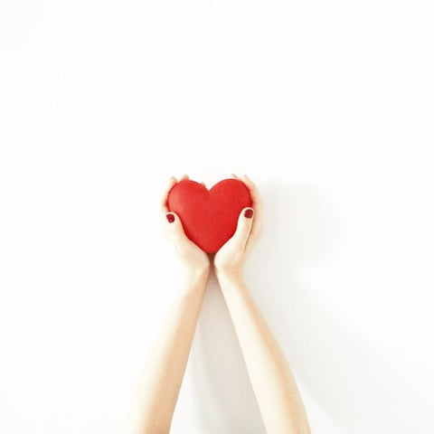 Hands perfectly fit around a red heart