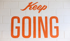 """""""keep going"""" painted on white brick wall"""
