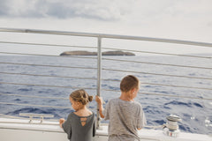 two children on a boat looking out at the ocean to see whales