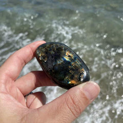 Black and blue metallic polished labradorite pebble held in front of ocean