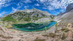 bright blue lake surrounded by sedimentary rock