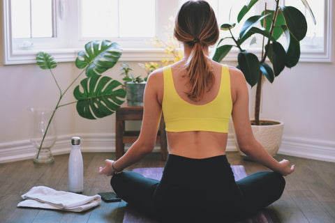 Back view of woman sitting on yoga mat next to water bottle and towel