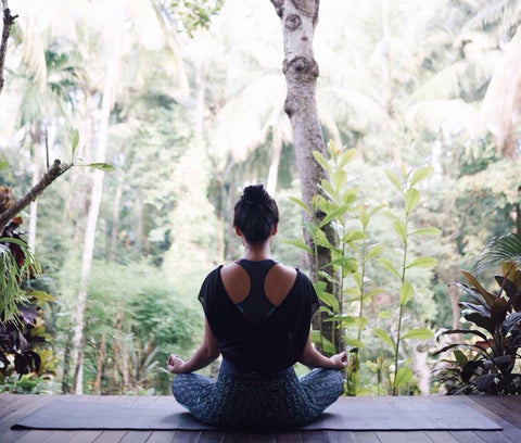 Back view of woman meditating while facing the rain forest